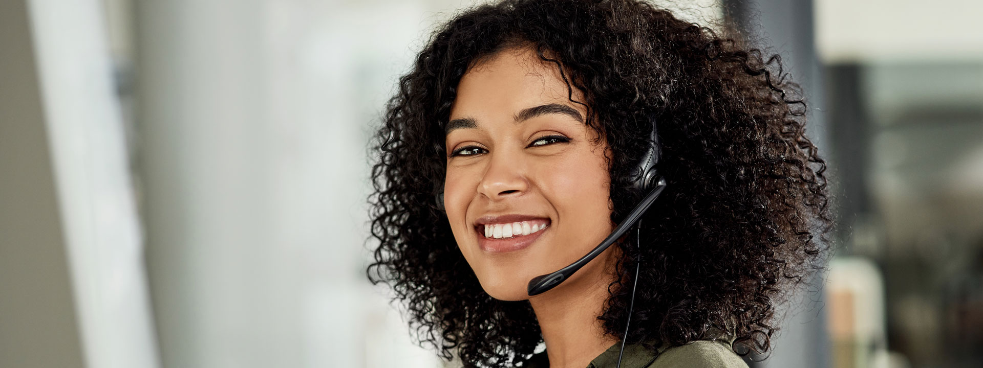 Women using telephone headset looking at camera