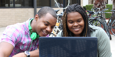 Image of male and female student using laptop on campus