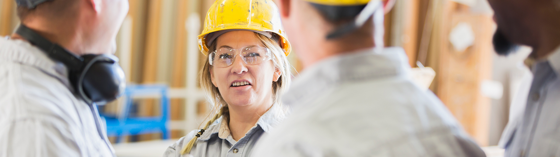 Female worker with hard hat speaking to others